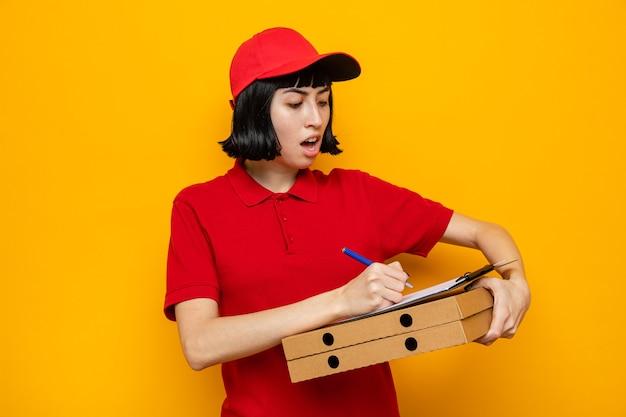 Giovane ragazza delle consegne caucasica sorpresa che tiene scatole per pizza e guarda gli appunti