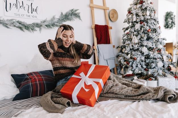 Giovane donna caucasica sorpresa con grande regalo di natale mentre era seduto su un letto a casa vicino all'albero di natale.