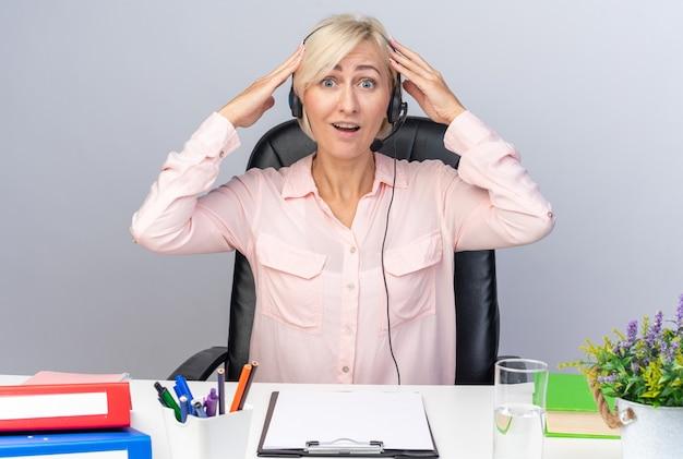 Sorpreso giovane operatore di call center femminile che indossa l'auricolare seduto al tavolo con strumenti da ufficio mettendo la mano sulla testa isolata sul muro bianco