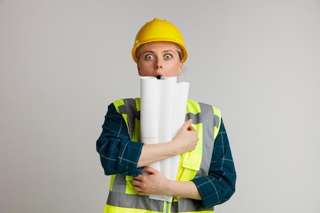 Giovane operaio edile femminile sorpreso che indossa il casco di sicurezza e la maglia di sicurezza che abbraccia i documenti