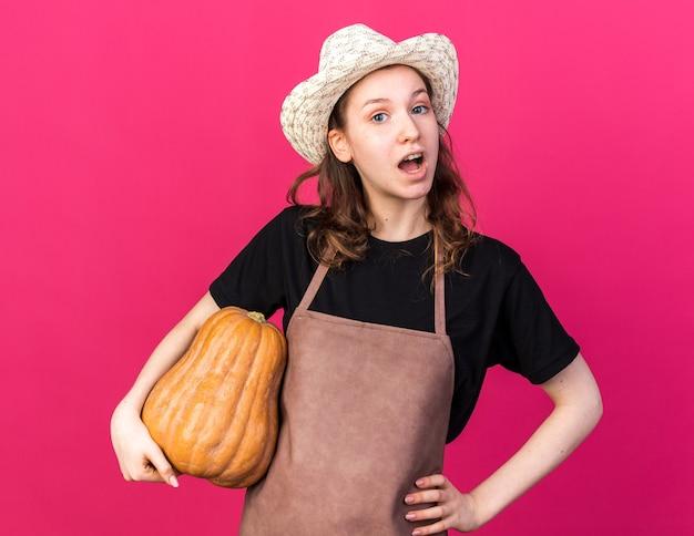 Sorpreso giovane giardiniere femminile che indossa un cappello da giardinaggio tenendo la zucca che mette la mano sull'anca isolata sulla parete rosa