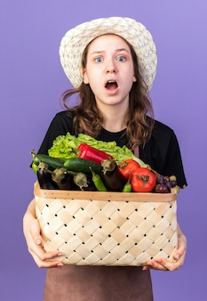 Sorpreso giovane giardiniere femminile che indossa un cappello da giardinaggio che tiene cesto di verdure