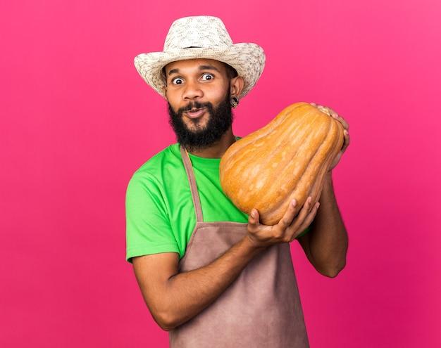 Sorpreso giovane giardiniere afroamericano che indossa un cappello da giardinaggio che tiene in mano una zucca isolata sul muro rosa