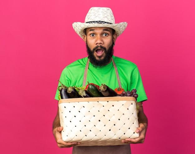 Sorpreso giovane giardiniere afro-americano che indossa un cappello da giardinaggio con cesto di verdure