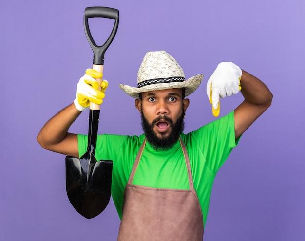 Sorpreso giovane giardiniere afro-americano che indossa un cappello da giardinaggio con guanti che tengono i punti di vanga verso il basso