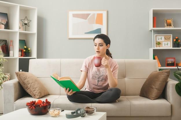 Ragazza sorpresa che si siede sul libro di lettura del sofà che tiene tazza di tè dietro il tavolino da caffè in soggiorno