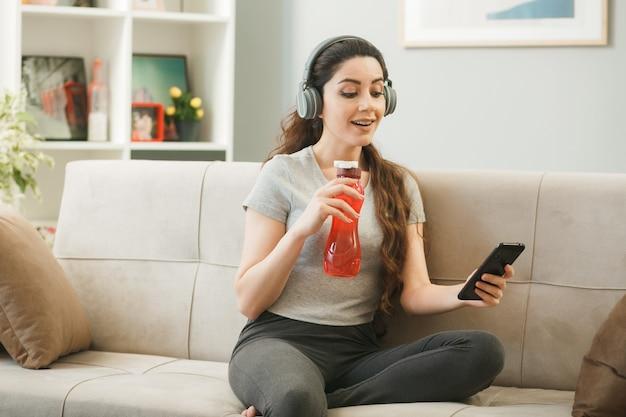Ragazza sorpresa che indossa le cuffie che tiene una bottiglia d'acqua e guarda il telefono in mano seduta sul divano nel soggiorno