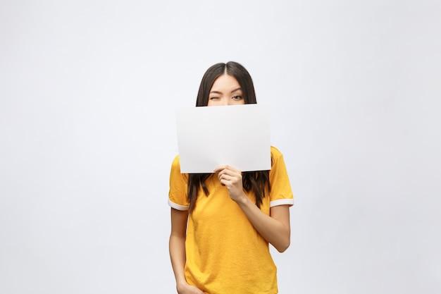 Ragazza sorpresa in camicia gialla con cartello bianco nelle mani