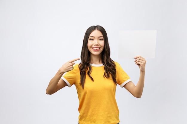 Ragazza sorpresa in camicia gialla con cartello bianco
