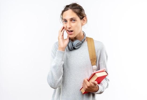 Sorpreso giovane studente che indossa uno zaino con le cuffie sul collo che tiene libri che mettono la mano sulla guancia isolata sul muro bianco con spazio di copia