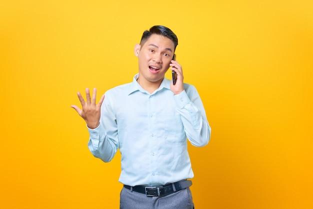 Sorpreso giovane uomo d'affari bello che parla su smartphone e mano alzata su sfondo giallo