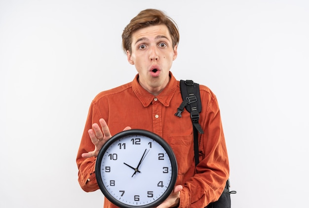 Sorpreso giovane bel ragazzo che indossa una camicia rossa con lo zaino che tiene l'orologio da parete isolato sul muro bianco
