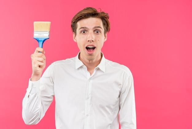 Sorpreso giovane bel ragazzo che indossa una camicia bianca che tiene il pennello isolato sul muro rosa