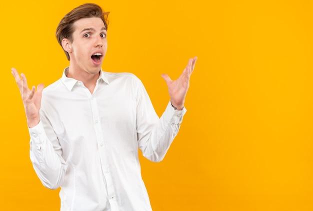 Sorpreso giovane bel ragazzo che indossa una camicia bianca che allarga le mani isolate sul muro arancione con spazio per le copie