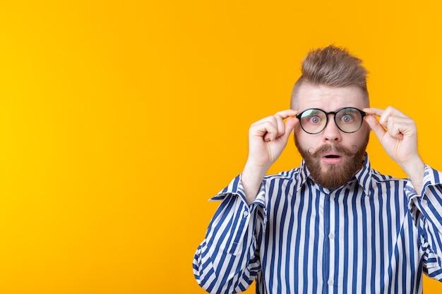 Uomo giovane hipster sorpreso con barba e baffi guarda attraverso gli occhiali in posa su un giallo