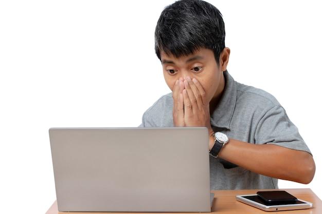 Giovane sorpreso sta passando in rassegna al suo computer portatile con smart phone e tablet sulla scrivania isolata