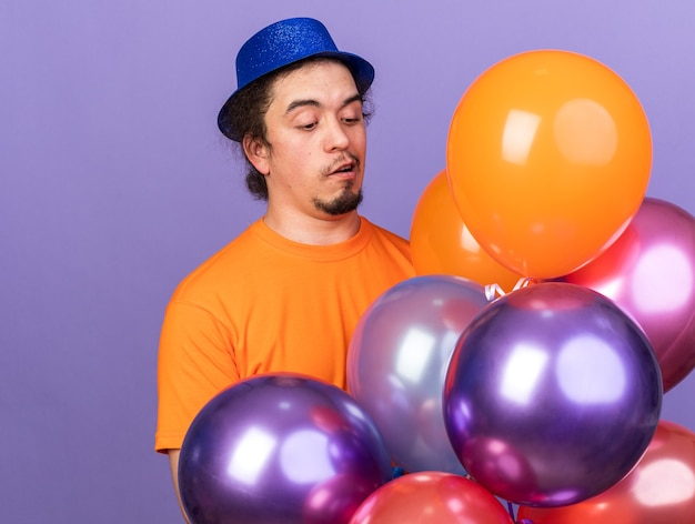 Giovane sorpreso che indossa un cappello da festa che tiene e guarda palloncini isolati sul muro viola