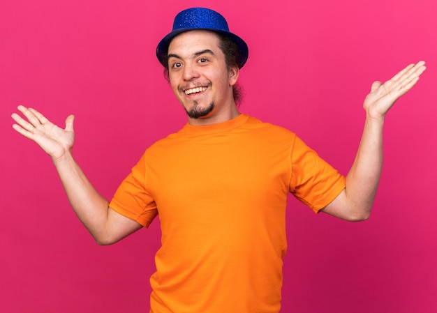 Sorpreso giovane che indossa il cappello da festa allargando le mani isolate sulla parete rosa