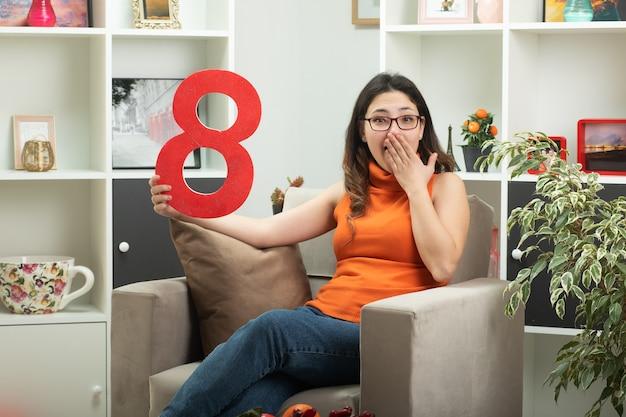 Giovane bella ragazza sorpresa in occhiali ottici che tiene la figura rossa otto e si mette la mano sulla bocca seduta sulla poltrona in soggiorno a marzo giornata internazionale della donna