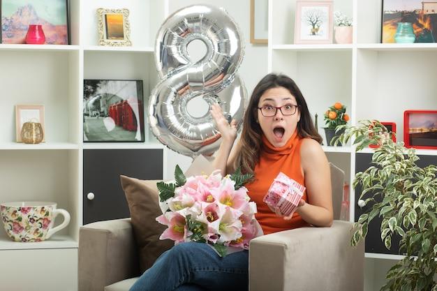 Sorpresa giovane bella donna con gli occhiali che tiene mazzo di fiori e confezione regalo seduta sulla poltrona in soggiorno a marzo giornata internazionale della donna