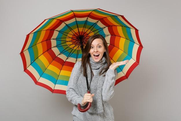 Giovane donna sorpresa in maglione grigio, sciarpa che allarga le mani, con ombrello colorato isolato su sfondo grigio. emozioni della gente di stile di vita sano di modo, concetto di stagione fredda. mock up copia spazio.