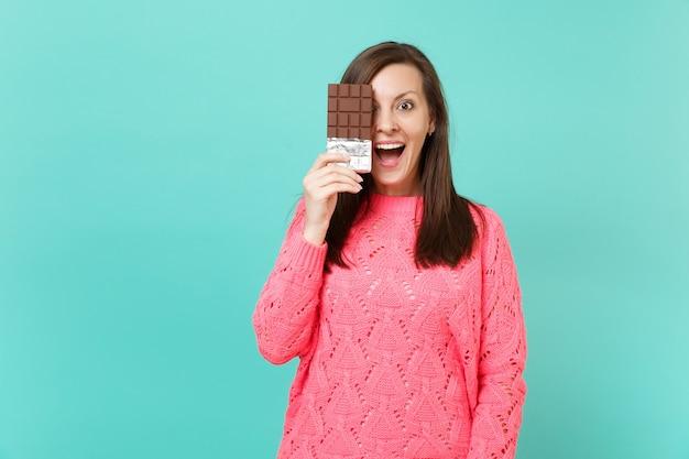 Giovane donna sorpresa in maglione rosa lavorato a maglia che tiene la bocca aperta tenere in mano, coprendo l'occhio con una barretta di cioccolato isolata sul fondo della parete blu in studio. concetto di stile di vita della gente. mock up copia spazio.