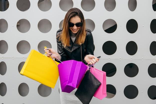 Sacchetto della spesa sorpreso di apertura della giovane donna su grey vicino al centro commerciale