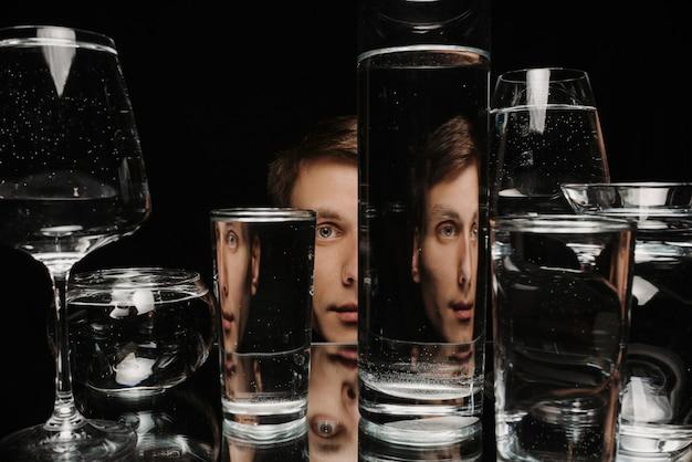 Ritratto surreale di un uomo che guarda attraverso bicchieri d'acqua con riflessi a specchio e distorsioni