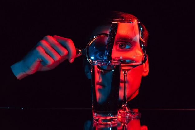 Ritratto surreale di un uomo che guarda attraverso una lente di ingrandimento e bicchieri di vetro con acqua con illuminazione rossa e blu
