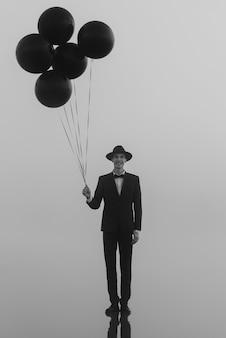 Ritratto surreale di un uomo vestito con un cappello con palloncini in mano sull'acqua al mattino nella nebbia