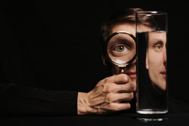 Ritratto surreale di un uomo attraverso una lente d'ingrandimento e un contenitore d'acqua
