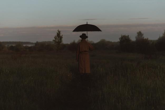 Silhouette surreale di un uomo vestito con un ombrello, in piedi con un impermeabile in un campo