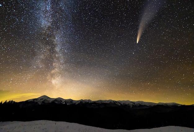 Vista surreale della notte in montagna con cielo nuvoloso blu scuro stellato