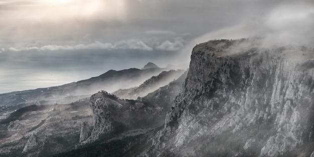 Paesaggio di montagna surreale con picchi nella nebbia