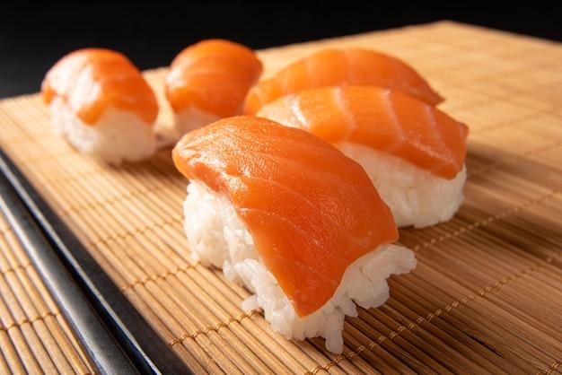 Sushi, bellissimo arrangiamento di sushi ricoperto di hashi su una stuoia di bambù