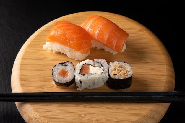 Sushi, bella disposizione di sushi in legno sulla superficie scura
