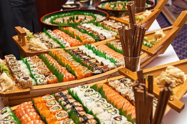 Barca di sushi con le bacchette sul tavolo bianco. barca di sushi