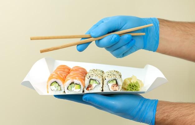 Concetto di consegna di sushi, corriere consegnato set di sushi in contenitore di carta eco a casa