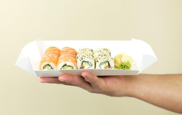 Concetto di consegna di sushi, uomo di corriere che tiene insiemi di sushi in un contenitore di carta usa e getta