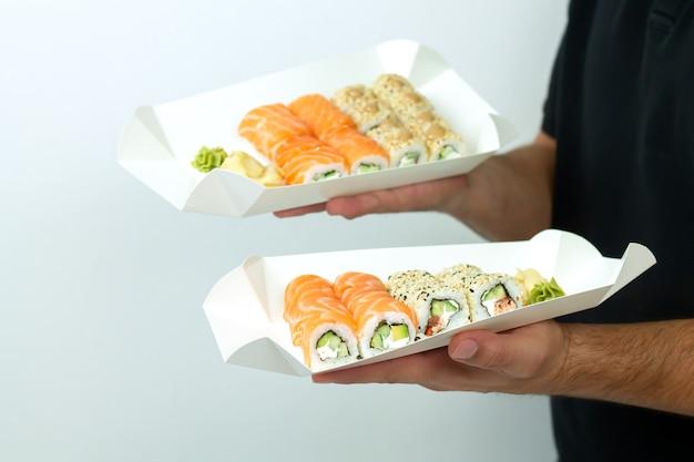Concetto di consegna di sushi, uomo di corriere che tiene insiemi di sushi in contenitori di carta eco