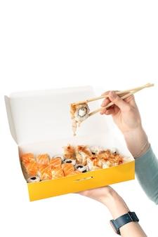 Concetto di consegna di sushi, ragazza con set di sushi in contenitore di carta usa e getta, scatole di carta ecologica