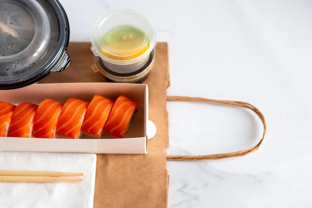 Consegna di sushi consegna di sushi delizioso e bellissimo in un pacchetto consegna di cibo a casa in artigianato