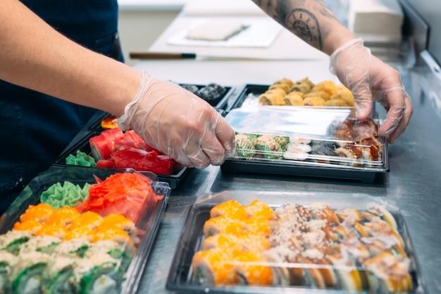 Consegna di sushi. molte varietà di sushi in una scatola di plastica sono pronte per la consegna.
