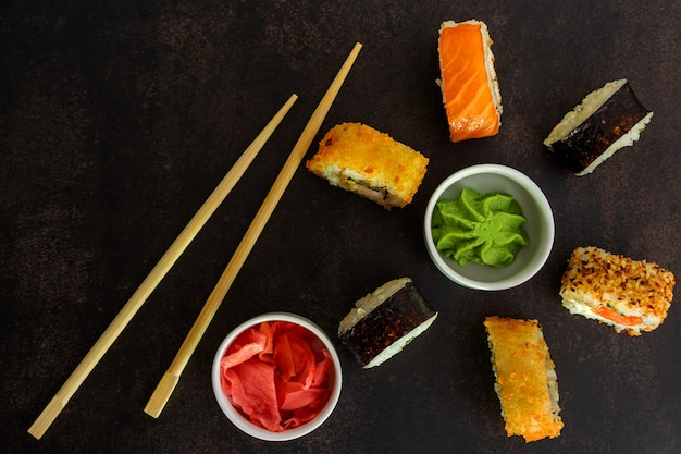 Sushi di diverse opzioni su una superficie scura, bacchette per rotoli vista dall'alto, con wasabi e zenzero