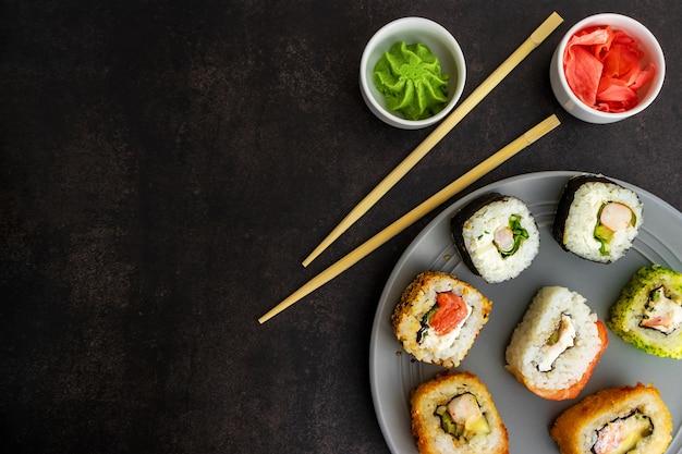 Sushi di diverse opzioni su un piatto grigio su uno sfondo vicino, vista dall'alto, con wasabi e zenzero