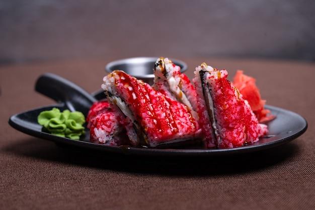 Sushi di riso rosso con pesce su un piatto nero.