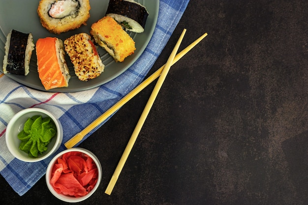 Sushi in un piatto grigio su uno sfondo scuro vista dall'alto con le bacchette i sushi, zenzero e wasabi