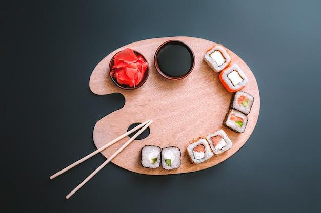 Sushi sdraiato su una tavolozza di legno. sfondo scuro.