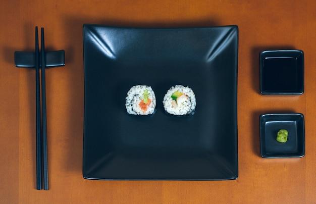 Rotoli di sushi maki presentati su un piatto con salse e bacchette
