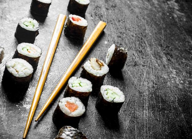 Sushi maki con le bacchette. sul tavolo rustico scuro
